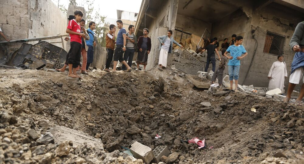 People gather at a site hit by a Saudi-led airstrike in Yemen's capital Sanaa May 27, 2015