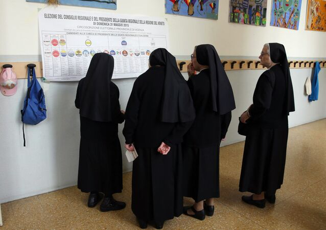 Nuns watch a list of candidates prior to cast their ballots for Italian regional elections in seven of the twenty country's regions and more than 700 municipalities, at a polling station in Vicenza, Italy, Sunday, May 31, 2015