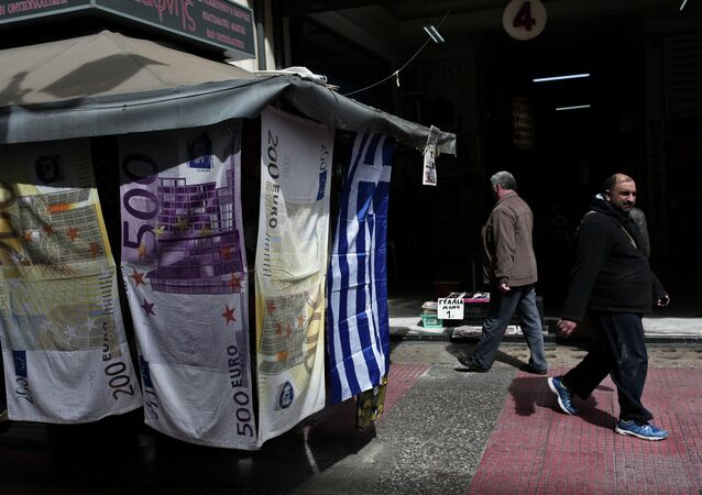 People walk past towels depicting Euro banknotes hanging outside a kiosk in Athens on March 22, 2015