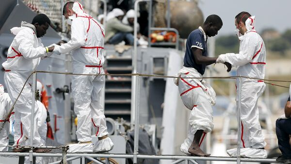 Migrants are helped to disembark from Italian Navy vessel Fenice as they arrive in the Sicilian harbour of Augusta, Italy, May 31, 2015 - Sputnik International