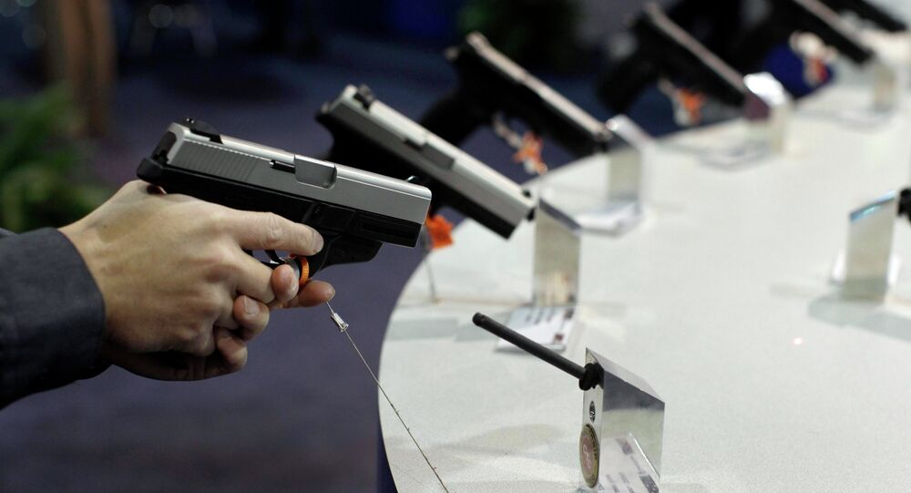A firearms retailer examines a Smith & Wesson 9mm pistol at the Shooting, Hunting and Outdoor Trade show, Jan. 18, 2011, in Las Vegas