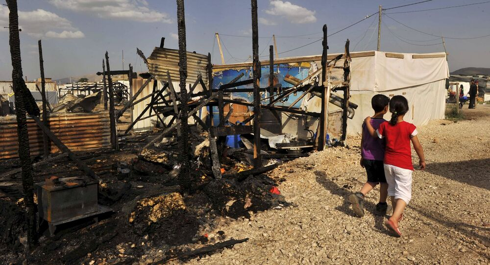 Children walk near the remains of tents that were burnt in a refugee camp for Syrian refugees in Lebanon's Bekaa Valley June 1, 2015.