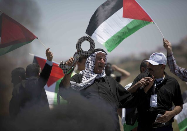 CORRECTS SECOND SENTENCE - A Palestinian holds a large key symbolizing the right of return for refugees during clashes after a rally marking Nakba Day at Hawara checkpoint near the West Bank city of Nablus, Saturday, May 16, 2015