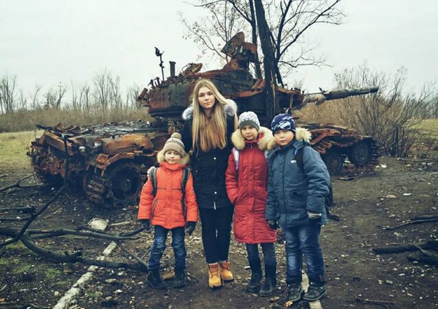 Powerlifting Champion Maryana Naumova poses with local children on a humanitarian trip to Luhansk.