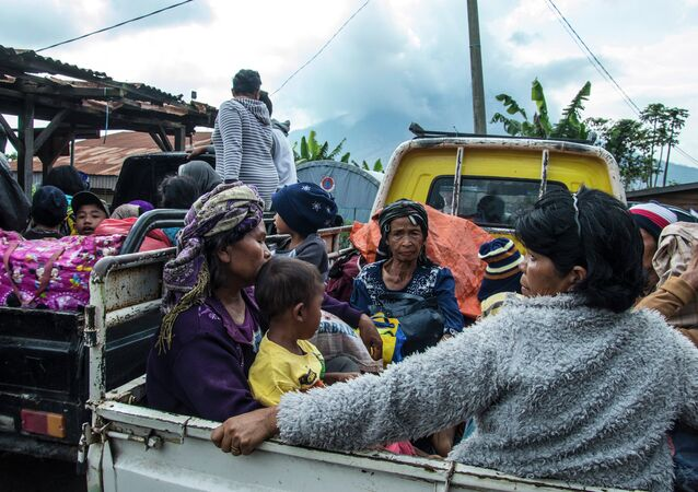 Residents are evacuated on farm vehicles at a village in the district of Karo near Mount Sinabung volcano, seen in the background, partly covered by clouds on June 3, 2015