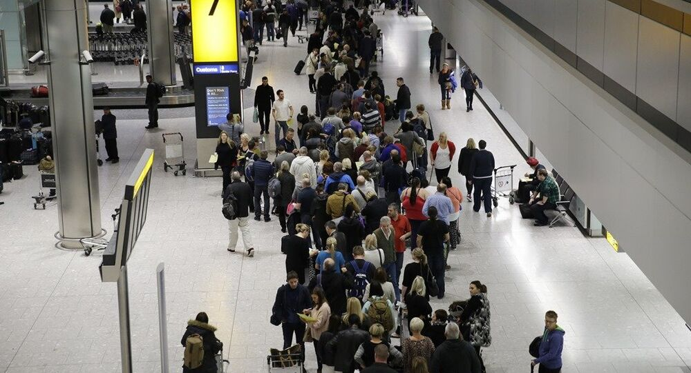 People queue in the luggage hall of Terminal 5 at Heathrow Airport in London.