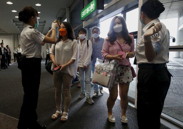 Flight passengers from Busan, South Korea, receive a temperature check upon their arrival at Hong Kong Airport in Hong Kong, China