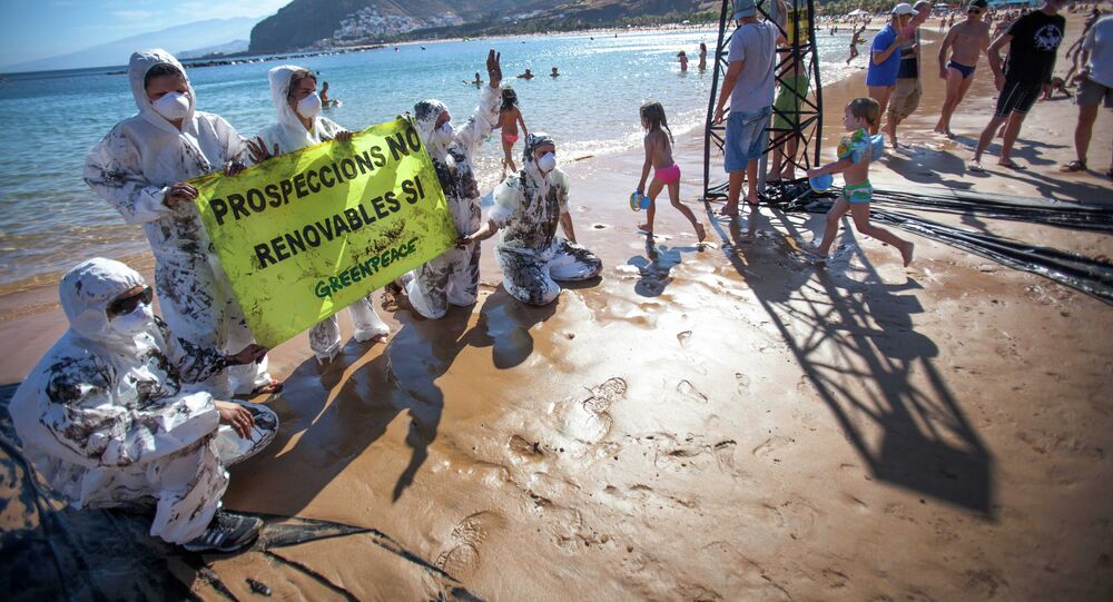 Greenpeace volunteers hold up a sign saying prospecting NO, Renewables YES on Playa de Las Teresitas north of Santa Cruz de Tenerife