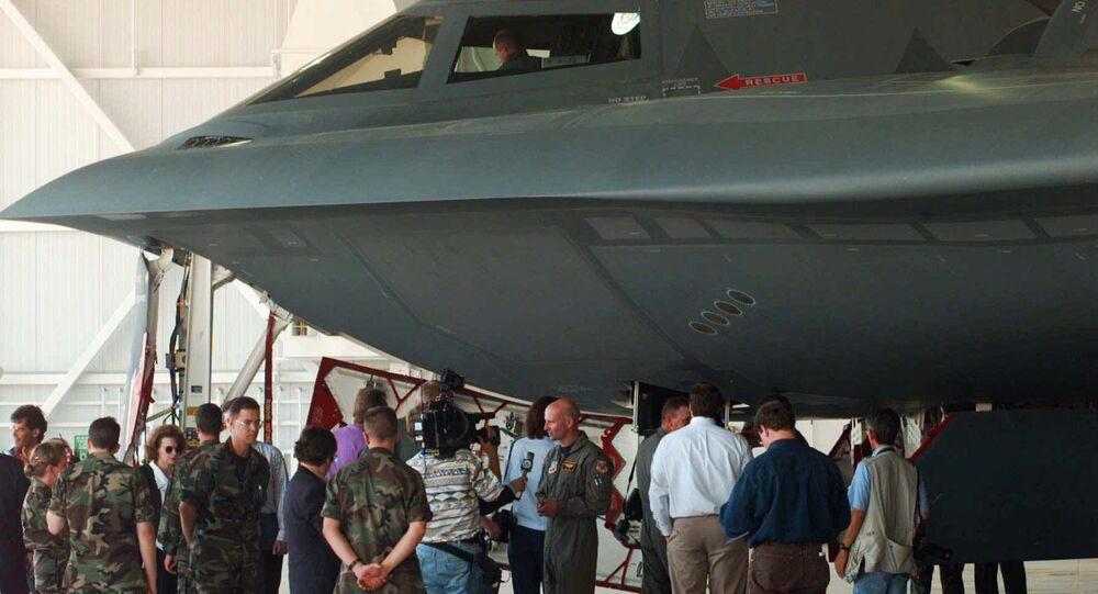 Reporters and Air Force personnel gather under a B-2 Stealth Bomber on Sept. 12, 1997.