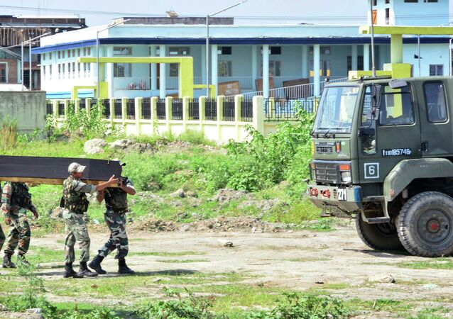 Indian security personnel carry the coffin of a victim's body after postmortem in India's northeastern state Manipur, India, Friday, June 5, 2015.