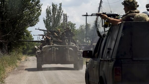 Members of the Ukrainian armed forces ride on an armoured personnel carrier as they patrol the area in the town of Maryinka, eastern Ukraine, June 5, 2015 - Sputnik International