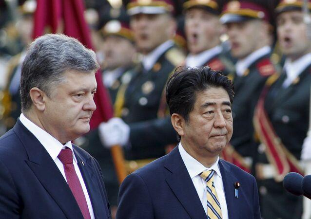 Japan's Prime Minister Shinzo Abe (R) and Ukraine's President Petro Poroshenko inspect honour guards during a welcoming ceremony in Kiev, Ukraine