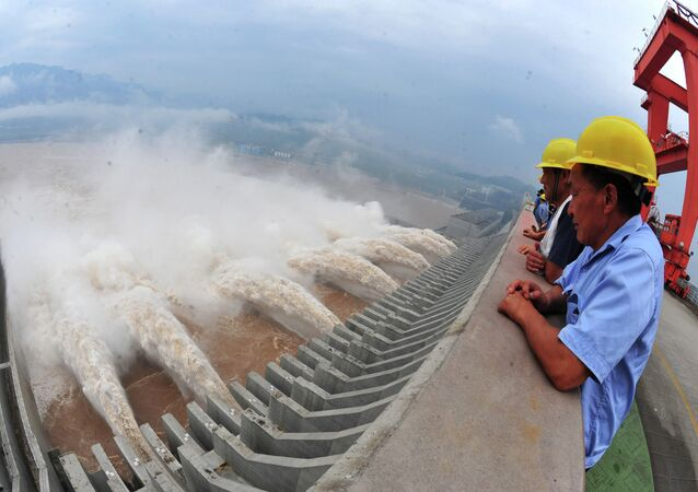 This picture taken on July 24, 2012 shows workers watching as water is released from the Three Gorges Dam, a gigantic hydropower project on the Yangtze river, in Yichang, central China's Hubei province