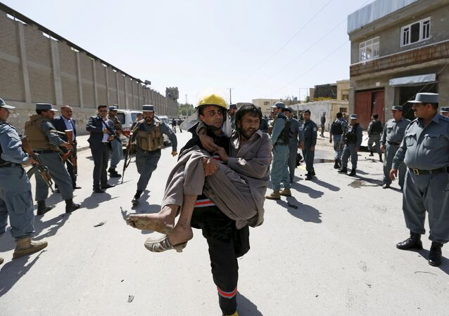 An Afghan policeman carries an injured man after an attack in Kabul, Afghanistan in this May 17, 2015 file photo