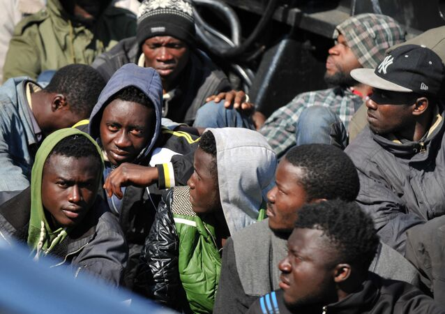 People wait after disembarking from tanker Maria Bottiglieriin carrying more than 110 Central African migrants, men and women, on April 15, 2015 in the port of Corigliano Calabro