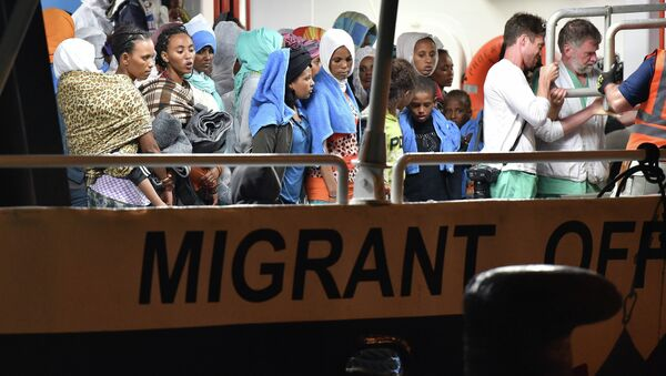 Migrants wait to disembark from the Migrant Offshore Aid Station (MOAS) ship Phoenix in the Sicilian port town of Augusta, Italy, Sunday, June 7, 2015 - Sputnik International