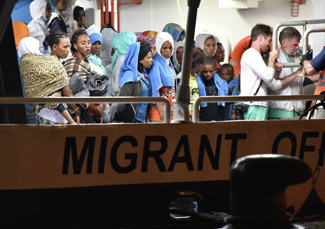 Migrants wait to disembark from the Migrant Offshore Aid Station (MOAS) ship Phoenix in the Sicilian port town of Augusta, Italy, Sunday, June 7, 2015