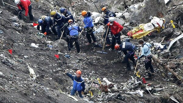In this March 26, 2015 file photo, rescue workers work on debris of the Germanwings jet at the crash site near Seyne-les-Alpes, France - Sputnik International