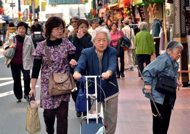 Elderly people stroll down a shopping precinct in Tokyo on October 28, 2011