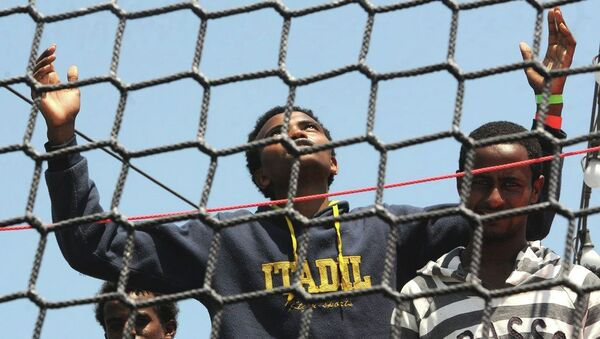 A migrant opens his arms as he waits to disembark from the German Navy ship Hessen at the Palermo harbor, Italy. - Sputnik International