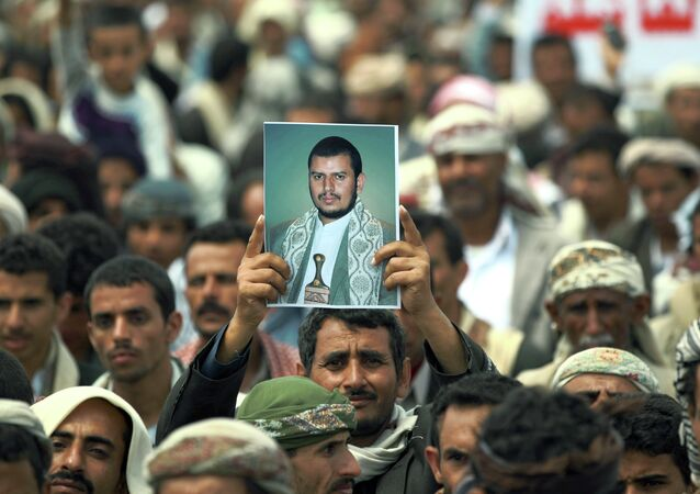 A Yemeni Shiite man holds up a picture of the Shiite movement leader Abdul-Malik al-Houthi during a demonstration organized by the Shiite Huthi movement to demand the government to rescind a decision to curb fuel subsidies on August 20, 2014