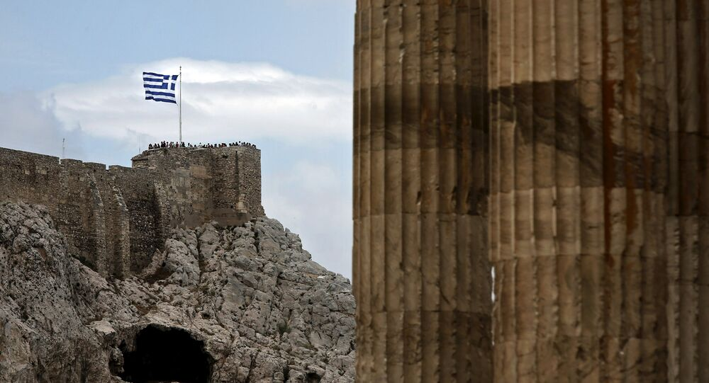 People stand next to a fluttering Greek national flag at the ancient site of the Athens' Acropolis as marble columns of the Temple of the Olympian Zeus are seen on the right June 7, 2015