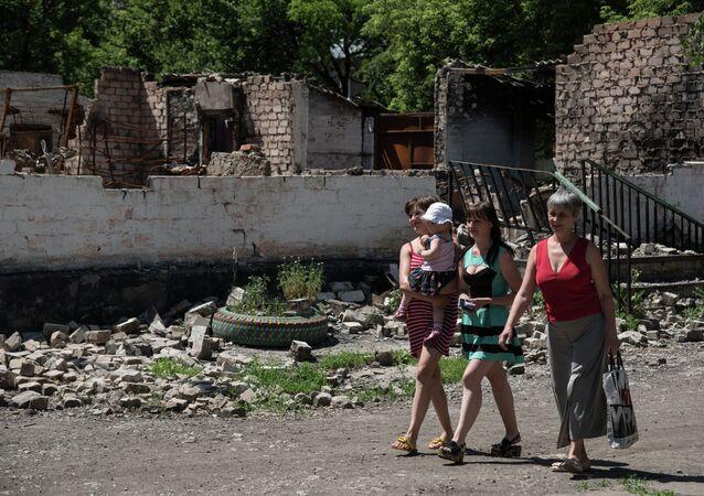 Residents walk in front of destroyed building as a result of shelling on June 8, 2015 in Novotoshkivske village, Donetsk region