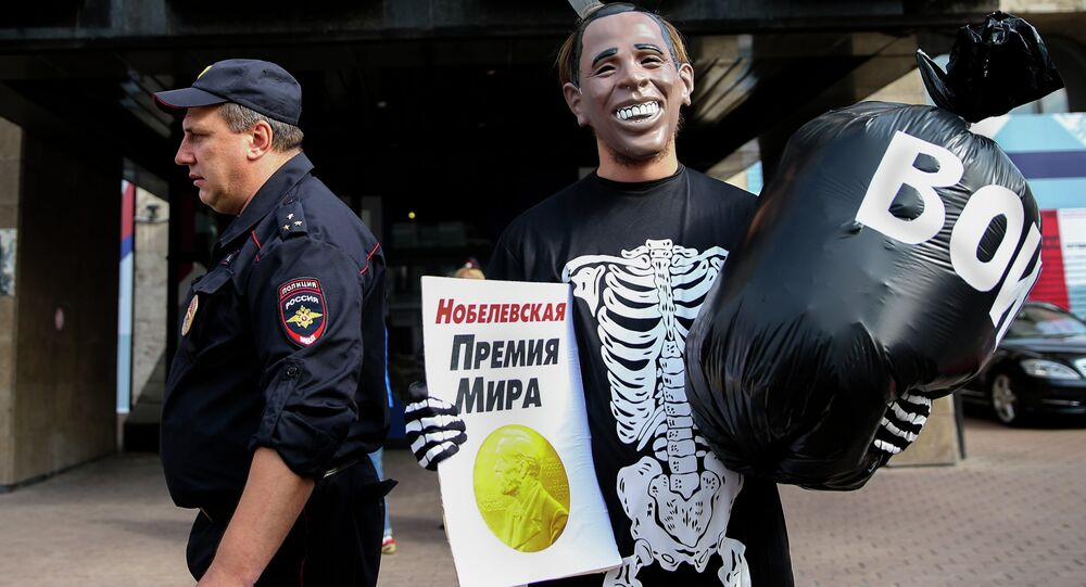 Russian Communist Party activist, wearing a mask depicting US President Barack Obama, holds a poster reading Nobel Peace Prize in one hand and a bag reading War in the other, takes part at a picket outside the UN mission in Moscow, Russia, Tuesday, Sept. 9, 2014