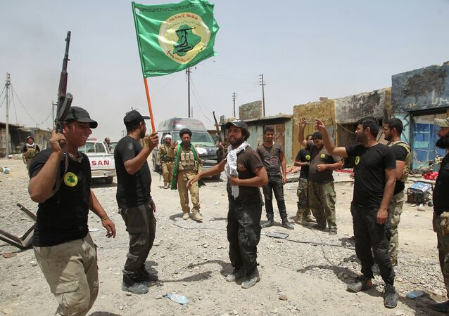 Iraqi Shiite fighters from the Popular Mobilisation force raise their flag in the city of Baiji, north of Tikrit, as they advance against the Islamic State jihadist group to try to retake the strategic town for a second time, on June 8, 2015