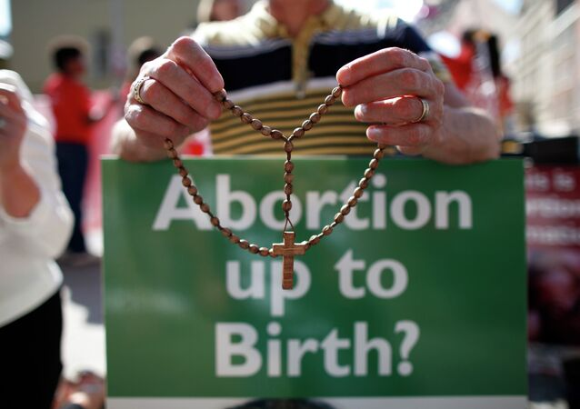 A file photo taken on July 10, 2013 shows a protester holding rosary beads and holding an anti-abortion placard in front of the gates of the Irish Parliament building in Dublin during a demonstration ahead of a vote to introduce abortion in limited cases where the mother's life is at risk