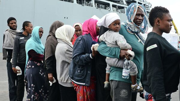 Migrants disembark from the Royal Navy ship HMS Bulwark upon their arrival in the port of Catania on the coast of Sicily on June 8, 2015 - Sputnik International