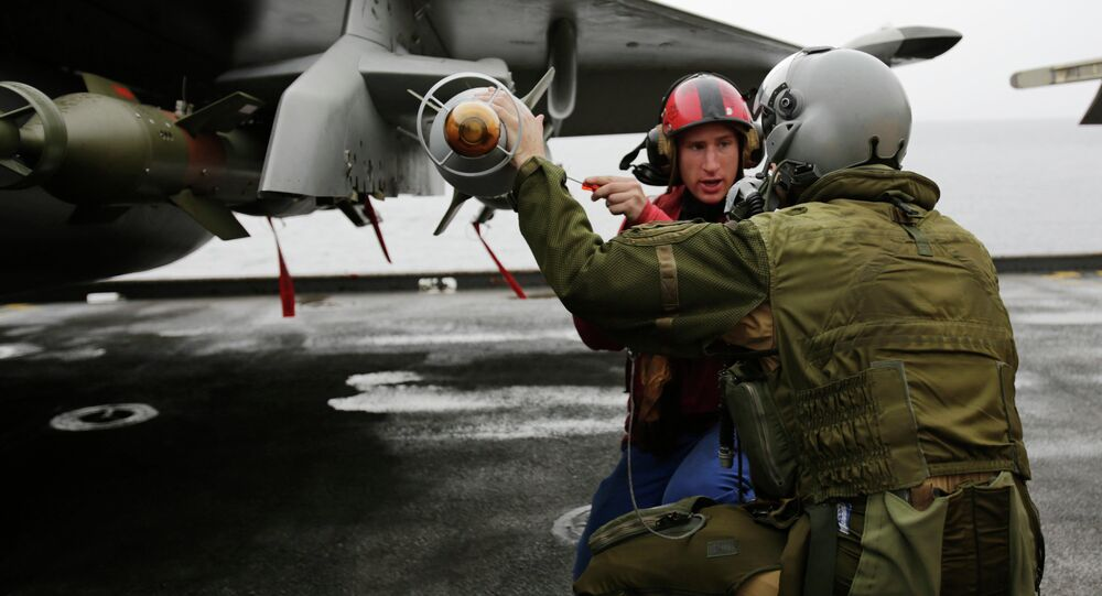 In this Wednesday, March 18, 2015 photo, a French pilot checks the bombs on his military plane before taking off from the flight deck of the French Navy aircraft carrier Charles de Gaulle in the Persian Gulf