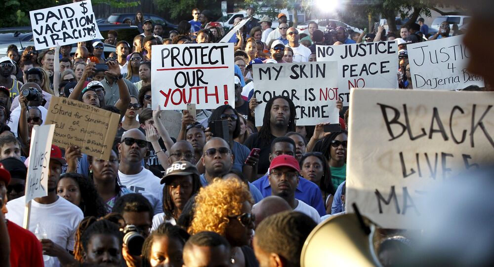 Protestors listen during a rally against what demonstrators call police brutality in McKinney, Texas June 8, 2015