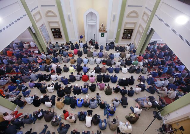 Muslim men sit on their prayer rug as visiting Imam Muhammad Adeyinka Mendes delivers his sermon before prayers in the mosque at the Islamic Society of Boston Cultural Center Friday, April 24, 2015, in Boston