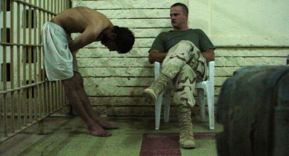 This is an image obtained by The Associated Press which shows a detainee bent over with his hands on the bars of a prison cell watched by a soldier in late 2003 at the Abu Ghraib prison in Baghdad, Iraq
