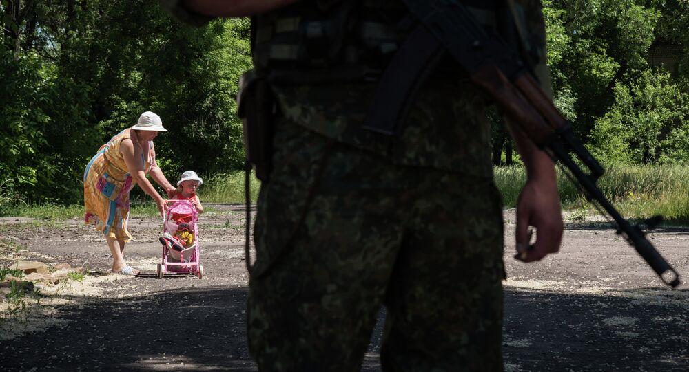 Woman walks with her child as Ukrainian serviceman stands guard on June 8, 2015 in Novotoshkivske village, Donetsk region