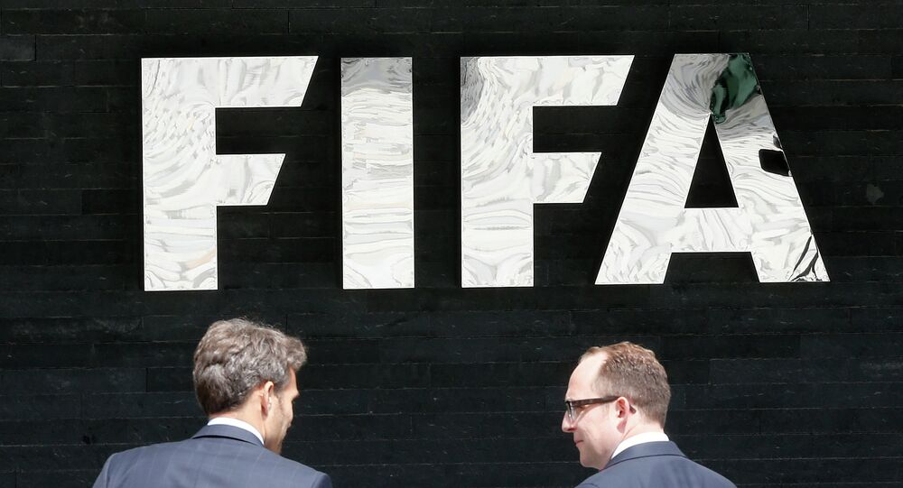 Two men talk to each other in front of the FIFA logo at the FIFA headquarters in Zurich, Switzerland, Wednesday, May 27, 2015