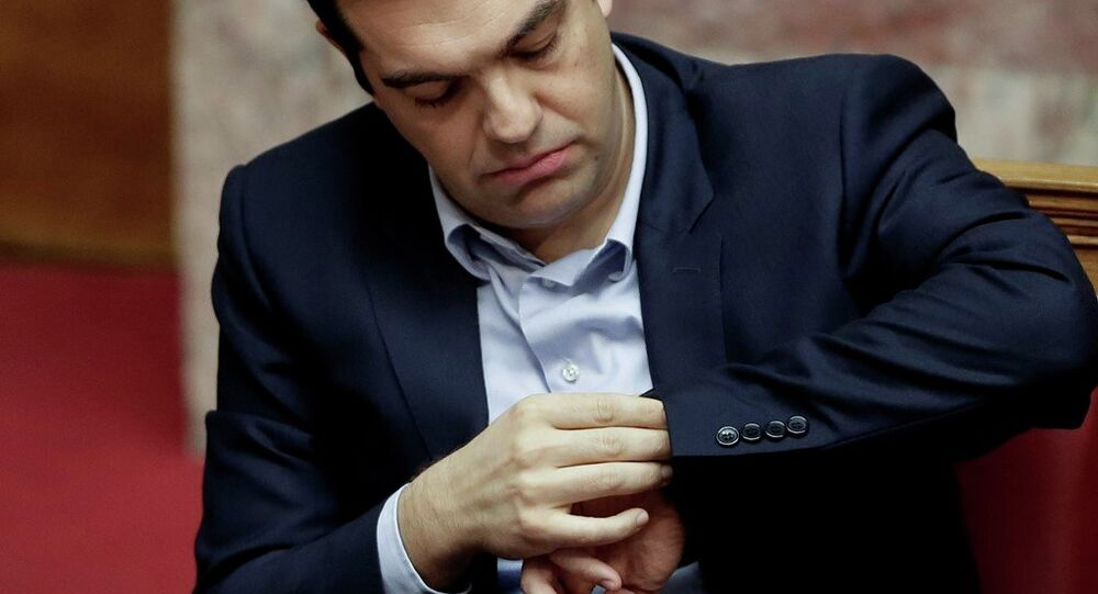 Greece's Prime Minister Alexis Tsipras looks at his watch during a parliament session in Athens,