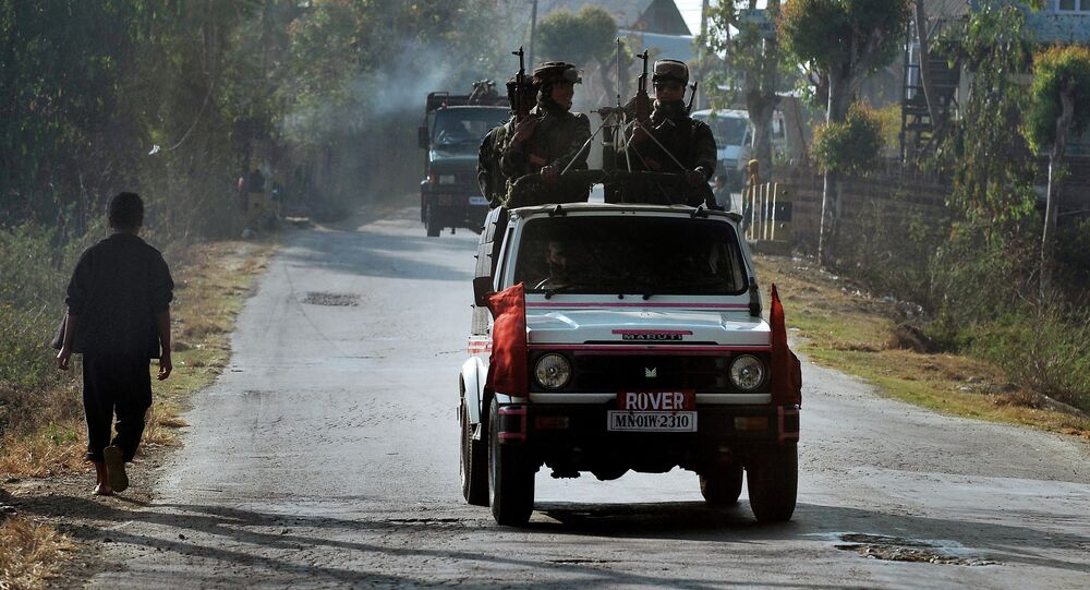 In this photograph taken on February 18, 2012, a vehicle carrying armed security personnel passes along a road on the outskirts of Imphal in the north eastern Indian state of Manipur