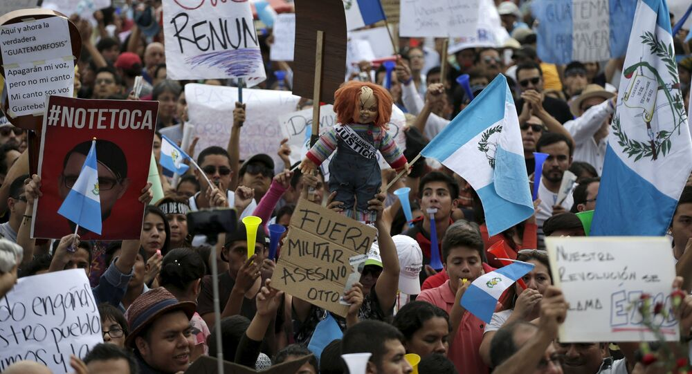 Protesters holds signs and a doll during a demonstration demanding the resignation of Guatemalan President Otto Perez Molina, in downtown Guatemala City, May 30, 2015