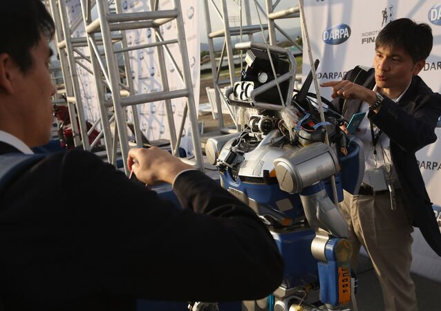 Roboticists take a closer look at the KAWADA Industries HRP-2 humanoid robot during the first day of the Defense Advanced Research Projects Agency (DARPA) Robotics Challenge at the Fairplex June 5, 2015 in Pomona, California