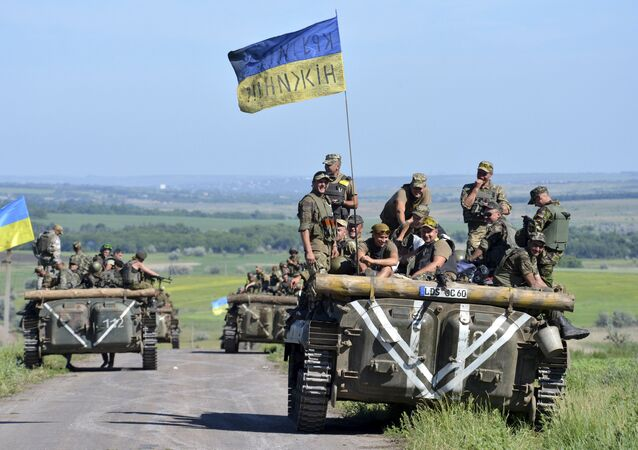 Members of the Ukrainian armed forces gather on armoured vehicles on the roadside near the village of Vidrodzhennya outside Artemivsk, Donetsk region, Ukraine, June 9, 2015