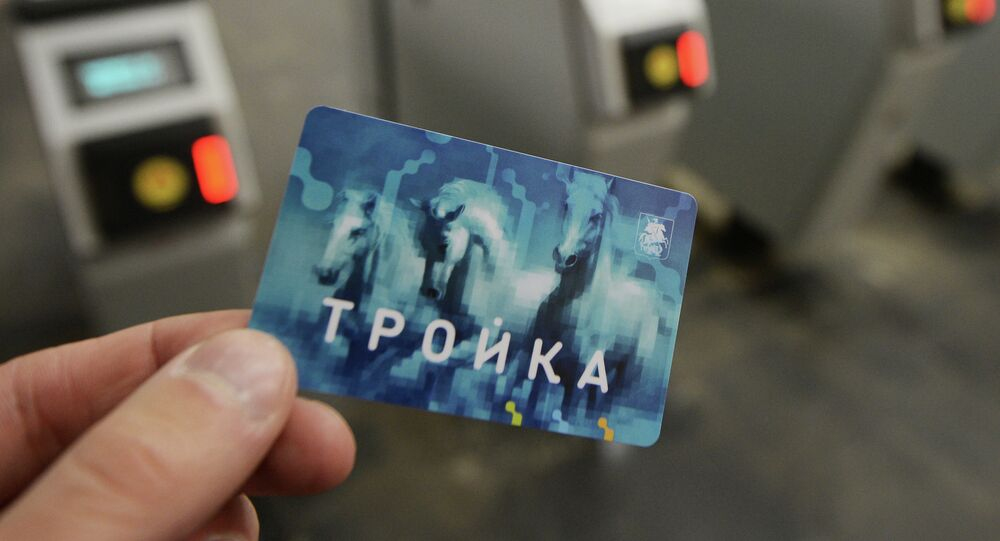 A man shows a Troika pass at a Moscow Metro station.