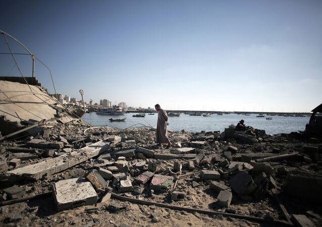 A Palestinian man inspects the damage of a police post, following an Israeli missile strike killing four boys from the same extended Bakr family, in Gaza City, Wednesday, July 16, 2014.