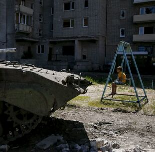 A boy sits on a swing near a building, which was damaged during fighting between Kiev and Donbass forces, as an armoured personnel carrier (APC) of the Ukrainian armed forces is seen nearby in Avdeyevka near Donetsk. June 7, 2015.