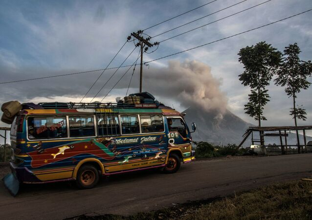 A public bus drives past Mount Sinabung volcano in Indonesia