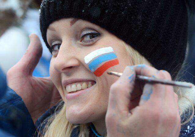 A young man paints a small Russian flag on the cheek of a girl
