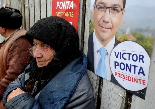 An elderly woman, back dropped by a campaign poster of Romanian Prime Minister Victor Ponta in 2011.