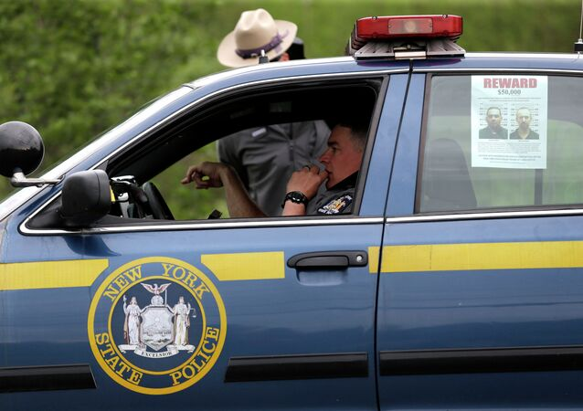 A wanted poster is displayed in the window of a state police officer's car near Dannemora, N.Y