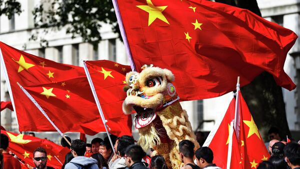 Chinese students hold a puppet depicting a dragon and  wave their national flags - Sputnik International